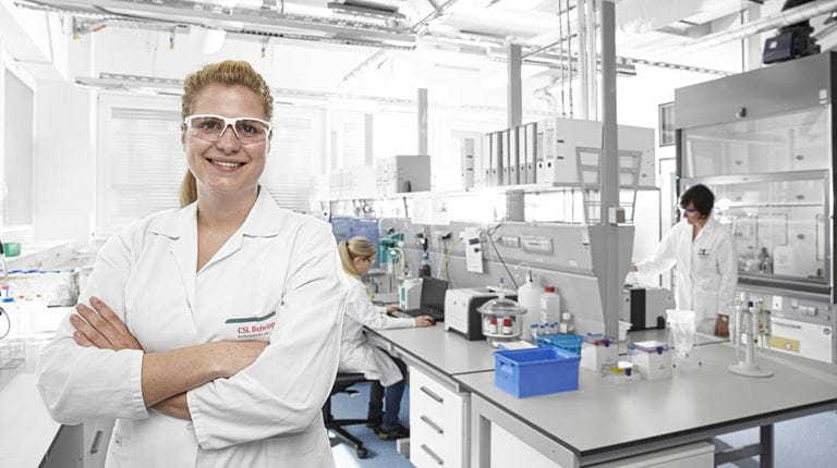 Junge Frau in weißem Kittel und Laborumfeld.