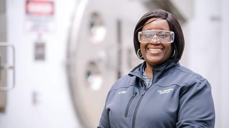 Lächelnde Mitarbeiterin mit Schutzbrille