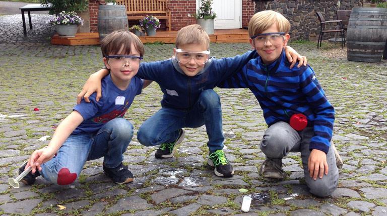 Drei Kinder knien auf einem Hof und tragen Schutzbrillen.
