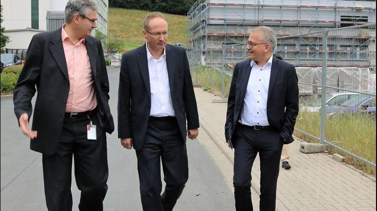 Drei Männer in Anzügen unterhalten sich und gehen an Baustelle vorbei.