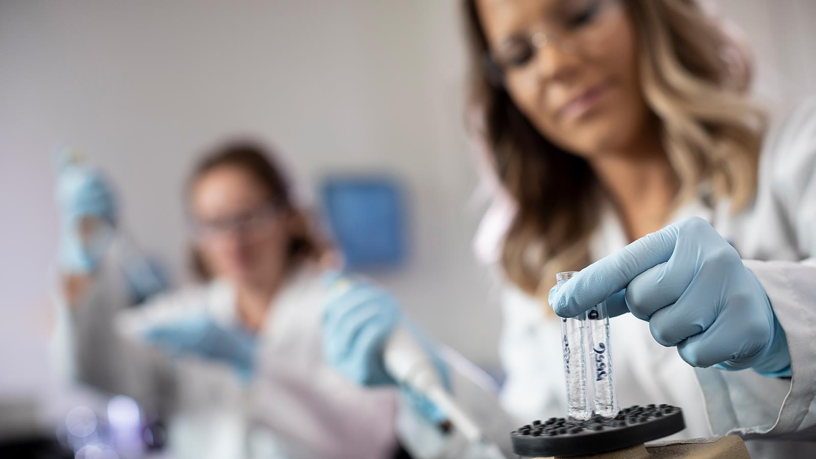 Two female researchers testing vials in a lab