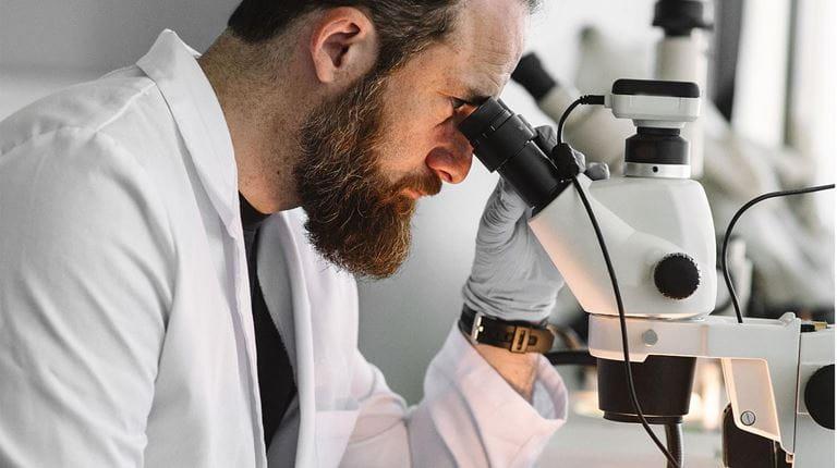 Forscher, der in ein Mikroskop schaut